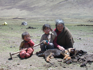 Tibetan grand-mother and her grand-children patting a dog. This behaviour is at high risk regarding Echinococcus transmission since villages and their surroundings are largely contaminated by dog faeces